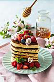 Heart-shaped pancakes with summer berries and honey