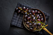 Bunch of delicious sweet ripe red grapes in bowl placed on checkered napkin on black surface