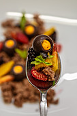 Spoon full of delicious chocolate dessert served with pieces of mango and strawberry and mint leaves in restaurant