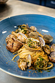 Palatable spaghetti served on plate with herbs and clams in restaurant