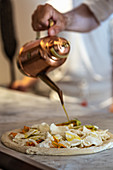 Crop anonymous Italian male chef pouring oil from metal teapot onto round pizza prepared for baking