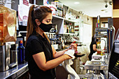Side view of female barman in protective mask wiping glass goblet with towel while working in bar