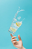 Unrecognizable female tossing glass of fresh water with ice and lemon