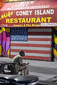 Man outside shuttered restaurant during Covid-19 outbreak