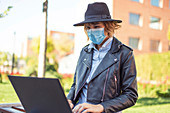Woman in face mask using laptop in park
