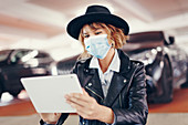 Woman in face mask using digital tablet
