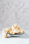 Homemade foam kisses with white chocolate and coconut shavings on a biscuit base