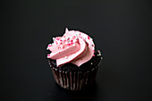 A chocolate cupcake with raspberry cream and sugar sprinkles