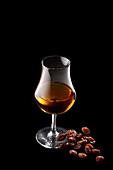 Ein Glas Rum daneben Rosinen
