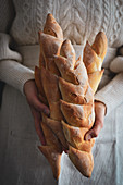 The woman holds baguette ears in her hands