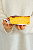 Woman is holding a plate with a piece of pumpkin cheesecake