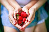 Hände von Mutter und Kind halten Erdbeeren