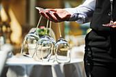 A waiter holding wine glasses