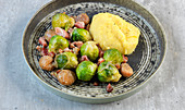 Fried Brussels sprouts and bacon with chestnuts and polenta
