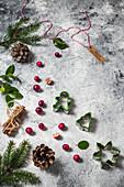 Weihnachtsstilleben mit Cranberries, Ausstechformen, Zweigen und Zapfen
