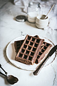 Oatmeal chocolate waffles with gooseberries served on white plate