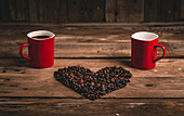 Ceramic mugs with hot drink placed on wooden table with grains arranged in shape of heart