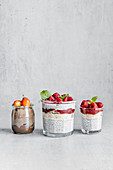 Composition of delicious puddings made from chia seeds yogurt topped with raspberry jam and cherry in glass jars on grey table
