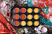 Metal baking dish with paper cupcake cups filled with colorful dough during pastry preparation for christmas holiday