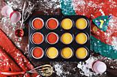 Muffinform mit buntem Teig gefüllt, zu Weihnachten