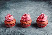 Yummy colorful cupcakes with whipped cream in red paper cups decorated with red rope placed on grey table