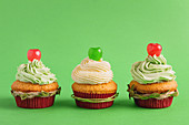Festive Christmas cupcakes with cherry on green background