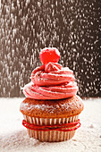 Sweet cupcake with pink frosting and red cherry sprinkled with white sugar powder served for christmas celebration