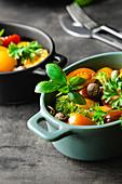 Gemüsesalat mit Tomaten und Pilzen, garniert mit Basilikum (Zutaten für Baked Eggs)