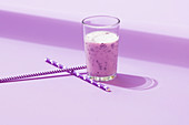 Glass of yummy cold natural blueberry smoothie placed with straw on lilac table