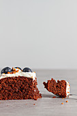 Slice of homemade chocolate sponge cake topped with fresh whipped cream and whole blueberries