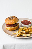 Hamburger with meat cutlet and golden buns decorated with mix of sesame seeds near crunchy toasted potato slices with spices and salsa barbecue on ceramic plate