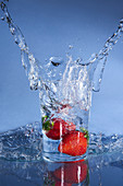 Cold tasty clean water spattering from glass with falling red gourmet strawberries