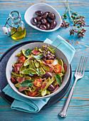 Spinach pasta leaves with tomatoes, dried ham and olives