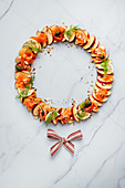 Festive apple carpaccio wreath with smoked salmon