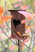 Rostiges Vogelhäuschen mit Herzöffnung
