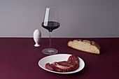 Still life with a glass of wine, beef steak and bread slice
