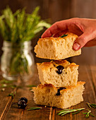 Taking piece of fresh homemade focaccia bread with olives and rosemary