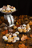 Various delicious Panellets arranged on wooden table with autumn leaves and cones for celebration of All Saints Day in Spain