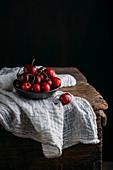 Frische Kirschen auf Holztisch mit weißem Musselintuch