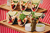 Traditional Mexican tacos served on wooden tray on table with various food