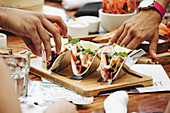 Crop anonymous people eating delicious traditional Mexican tacos served on wooden tray on table with various food and drinks