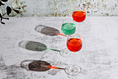 Glasses filled with colorful liquids put on concrete surface