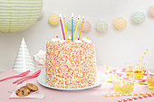 A birthday cake covered in sprinkles with five candles