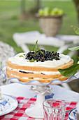 Layeredc ake with bramble jam, slices of banana and vanilla flavoured whipped cream