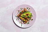 Homemade toasted bread from above with avocado, mango and aromatic herbs on pink background