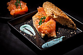 Smoked salmon and fennel herb on top of seeded bread on a dark plate and dark table