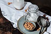 Glaskrug mit veganer Mandelmilch und Schälchen mit Mandeln