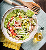 Healthy delicious salad with fresh tomatoes and lettuce with green olives and chicken served in bowl