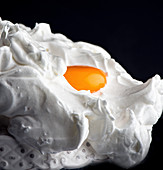 Raw whole egg yolk placed on whipped egg white against black background