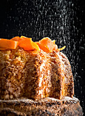 Soft carrot cake with falling particles of sweet sugar powder on table